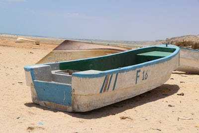 white and green canoe on brown sand during daytime somalia teams background