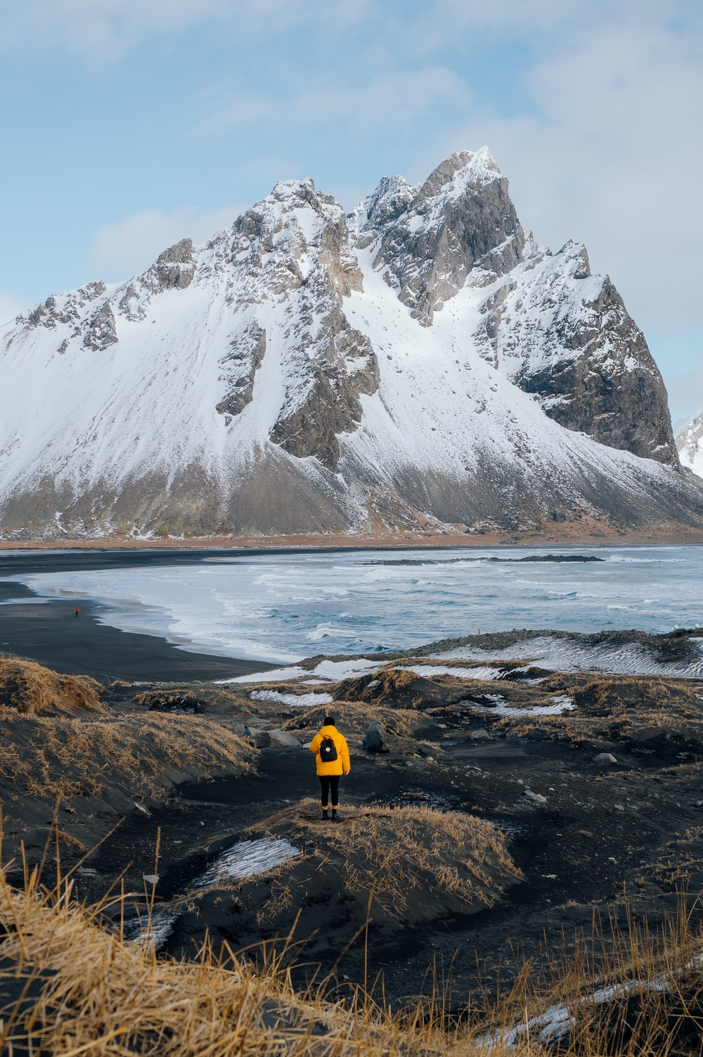 person in yellow jacket standing on brown rock near snow covered mountain during daytime