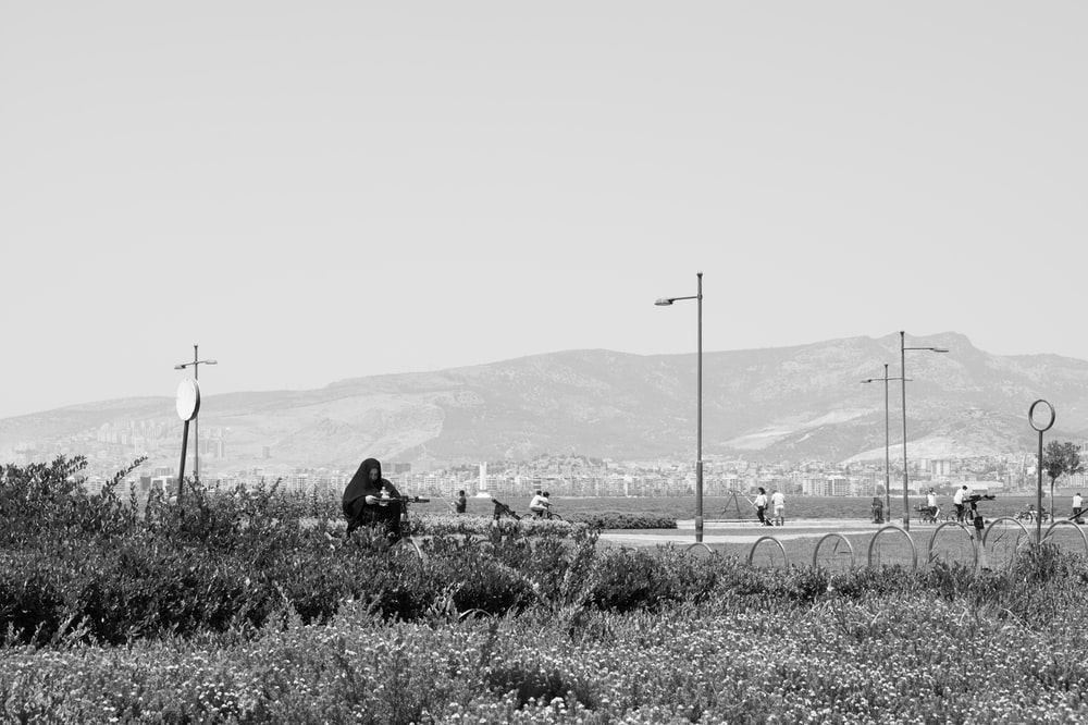 grayscale photo of person sitting on grass field