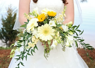 woman in white wedding dress holding white and yellow flowers