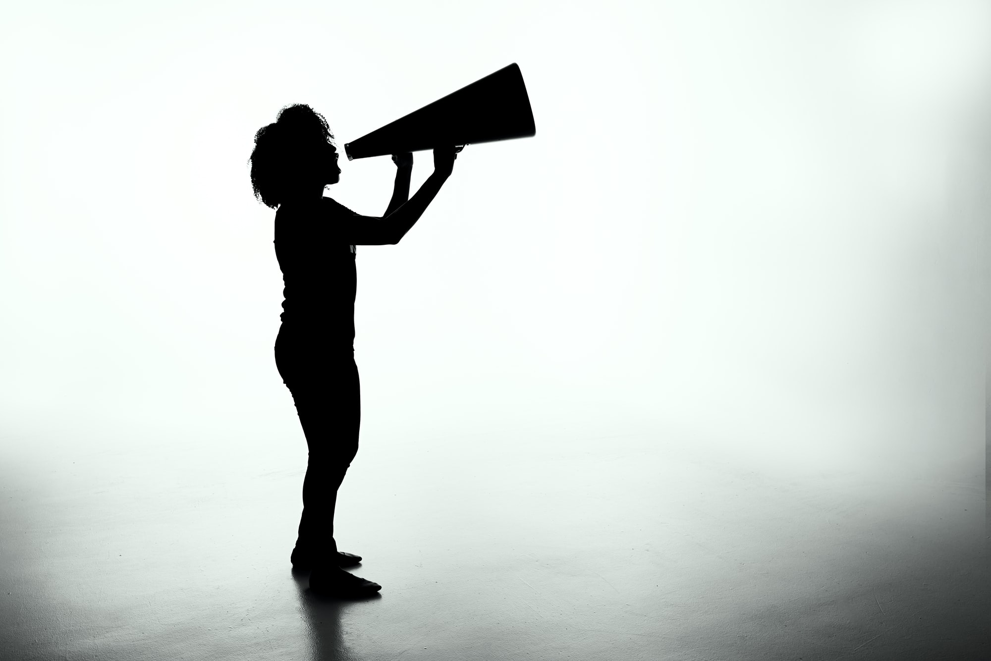 Silhouette of a female holding a analog megaphone.