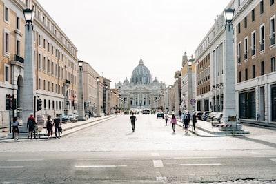 people walking on street near buildings during daytime vatican city teams background