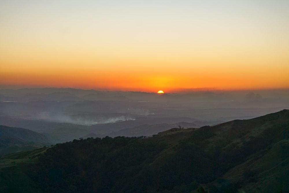 green mountain under orange sunset