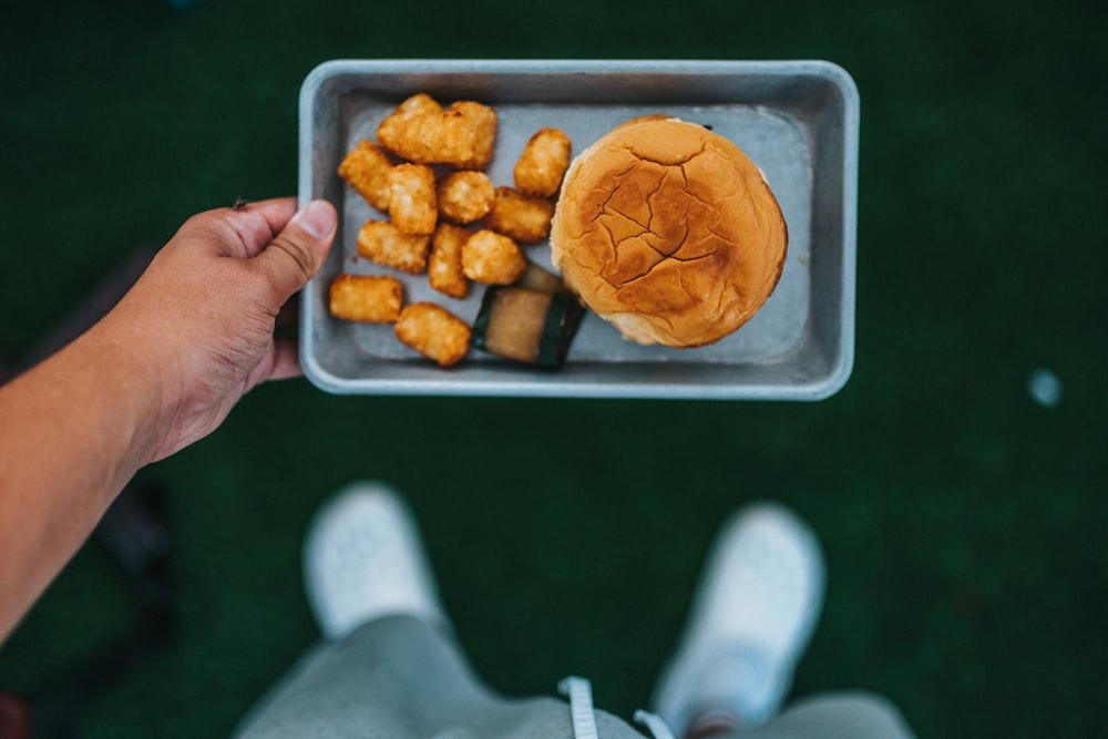 person holding tray with fried food