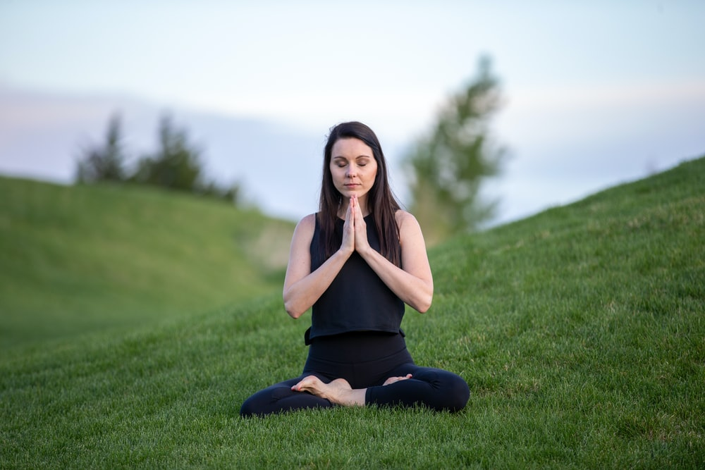 woman in black tank top and black pants sitting on green grass field during daytime