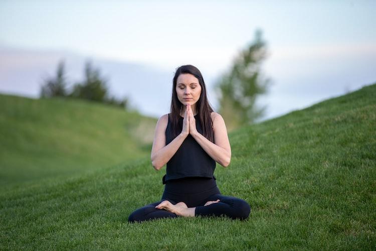 Mulher com roupas leves de ginástica sentada no gramado em posição namastê (de pernas cruzadas e com as palmas das mãos encostadas uma na outra) praticando meditação.