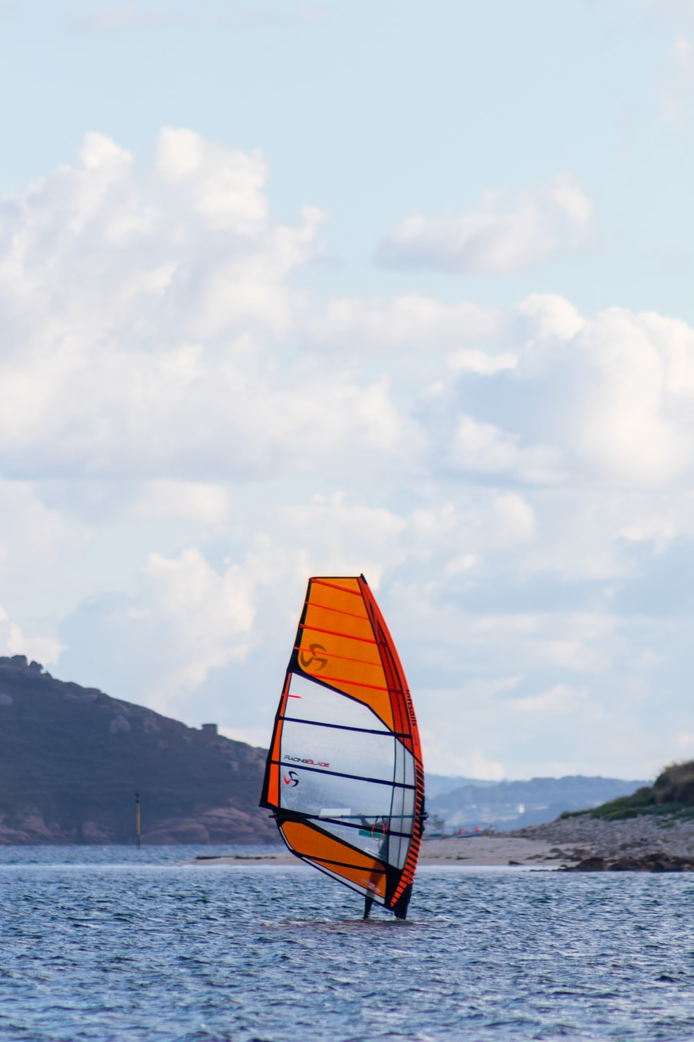 orange and white boat on sea shore during daytime