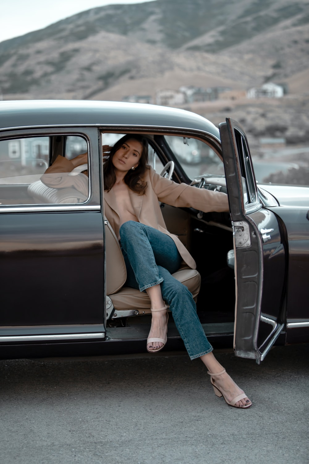 woman in blue denim jeans and brown jacket sitting on black car