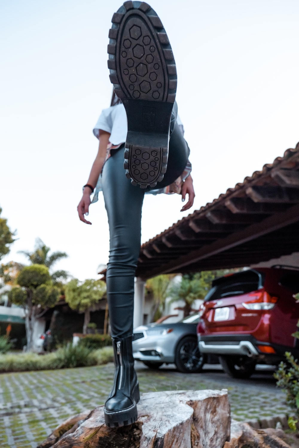woman in black and white shirt and blue denim jeans standing on red roof during daytime