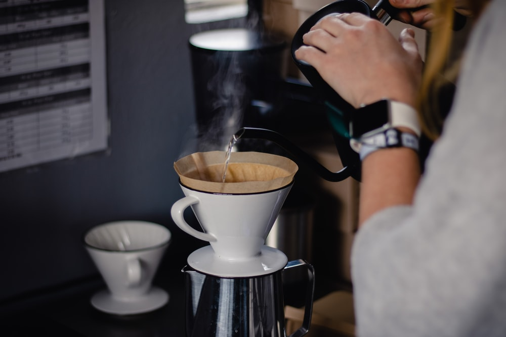 person pouring coffee on white ceramic mug