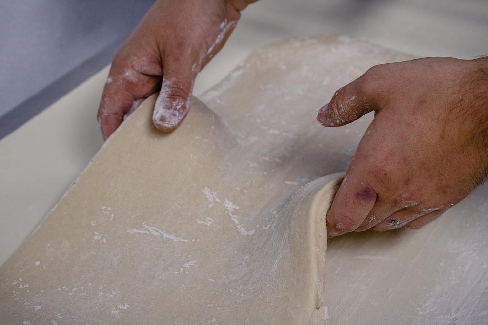person holding white dough with white powder