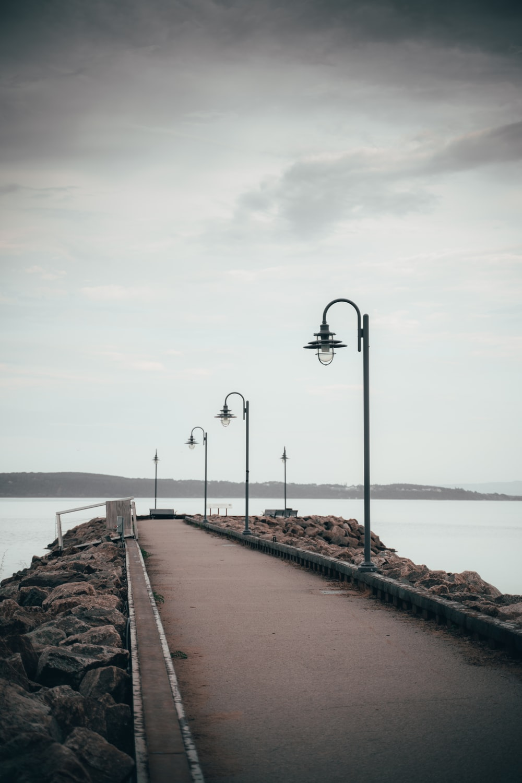 black steel light post on brown concrete dock during daytime