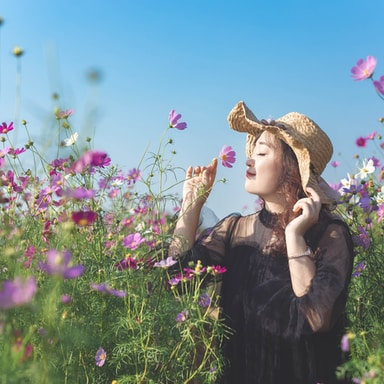 woman in black dress standing on flower field during daytime