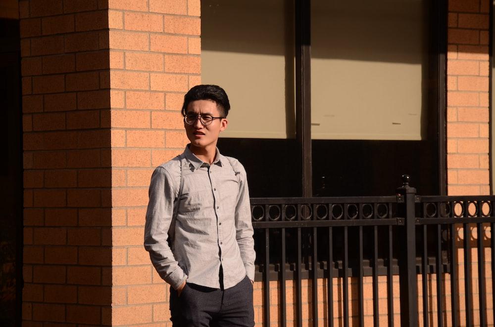 man in blue dress shirt and black pants standing near brown brick wall