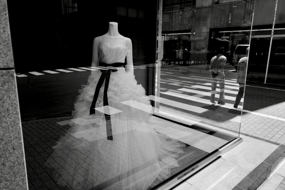 grayscale photo of woman in white dress standing on sidewalk