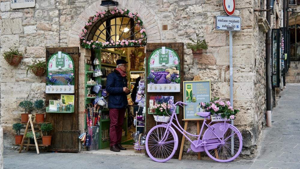 woman in black jacket standing beside purple bicycle