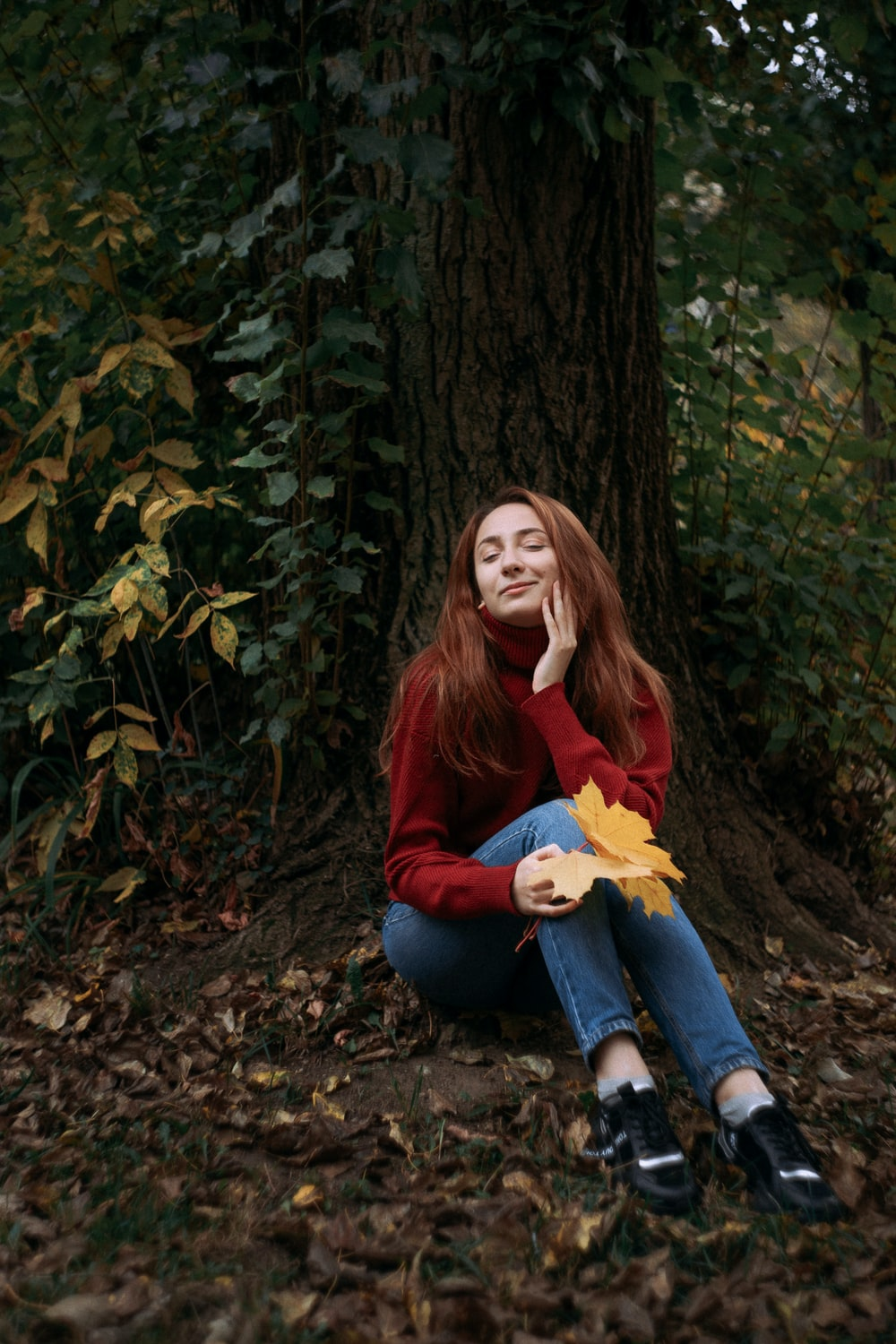 woman in red long sleeve shirt and blue denim jeans sitting on brown tree trunk