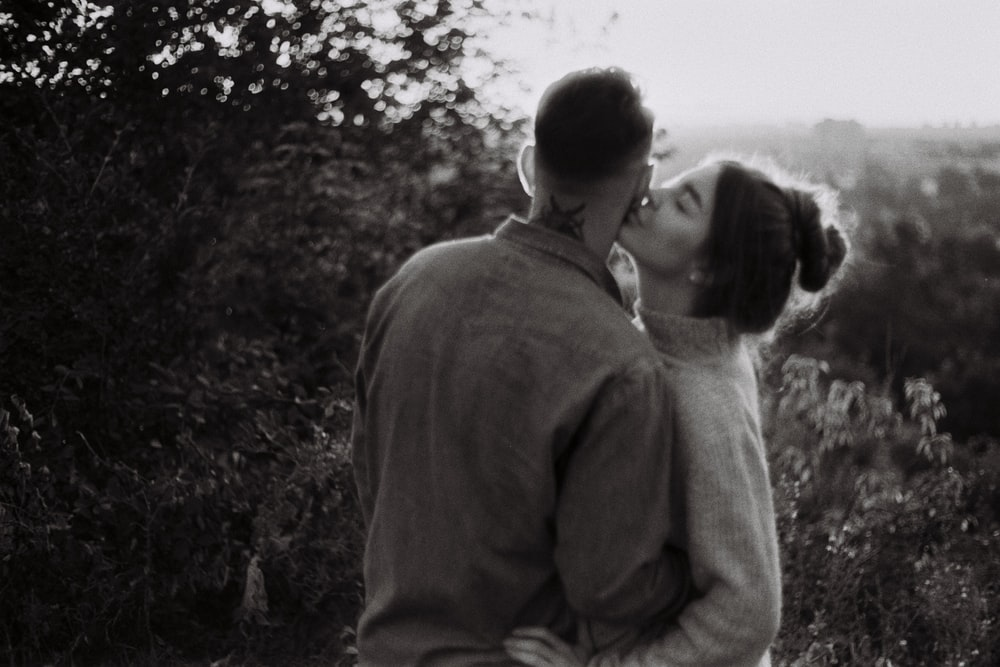 man and woman kissing in grayscale photography