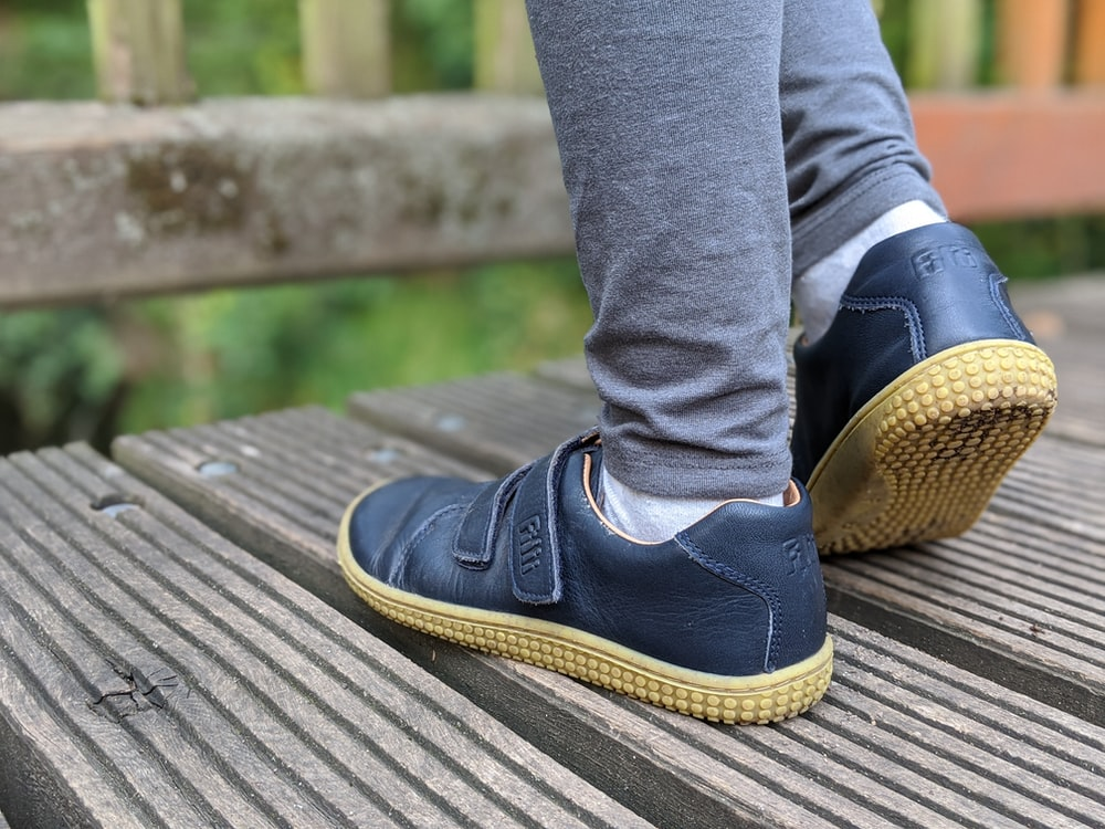 person in blue denim jeans and black and brown shoes