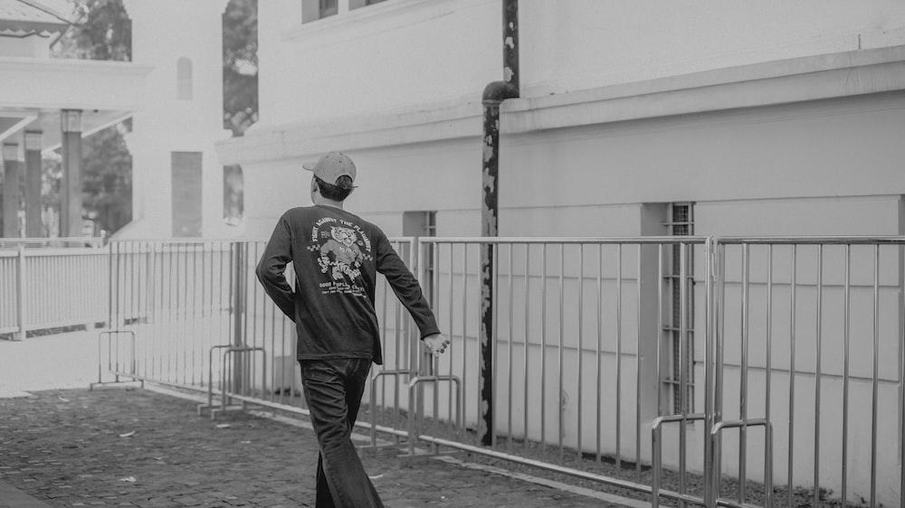 man in black jacket and pants walking on sidewalk