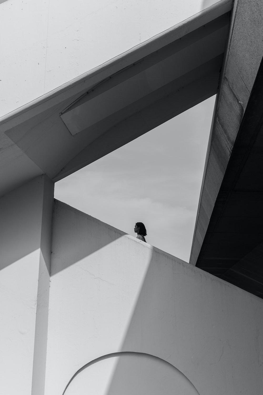 man in black jacket sitting on white concrete wall during daytime
