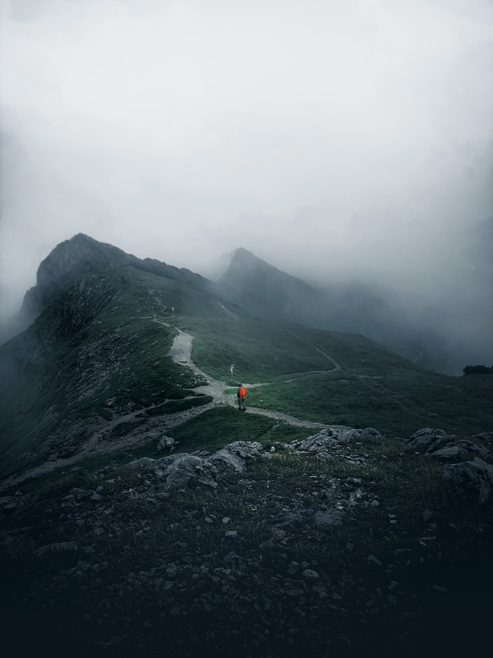 person in orange jacket standing on rock formation during foggy weather