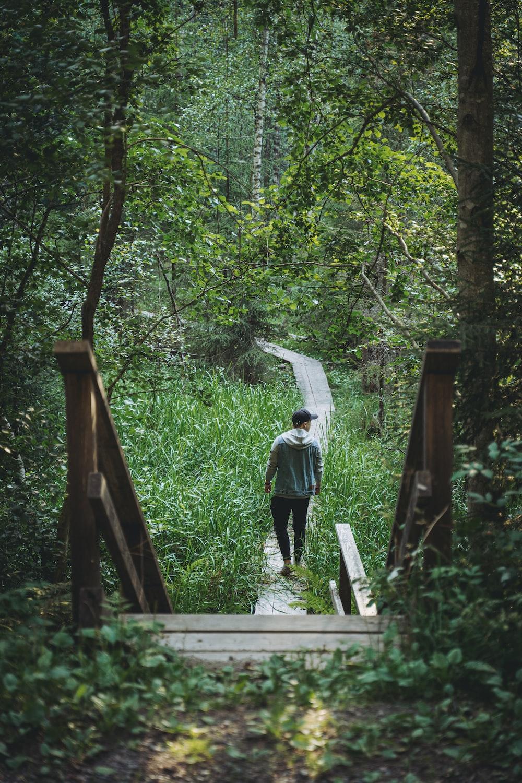 man in white shirt and black pants walking on brown wooden bridge
