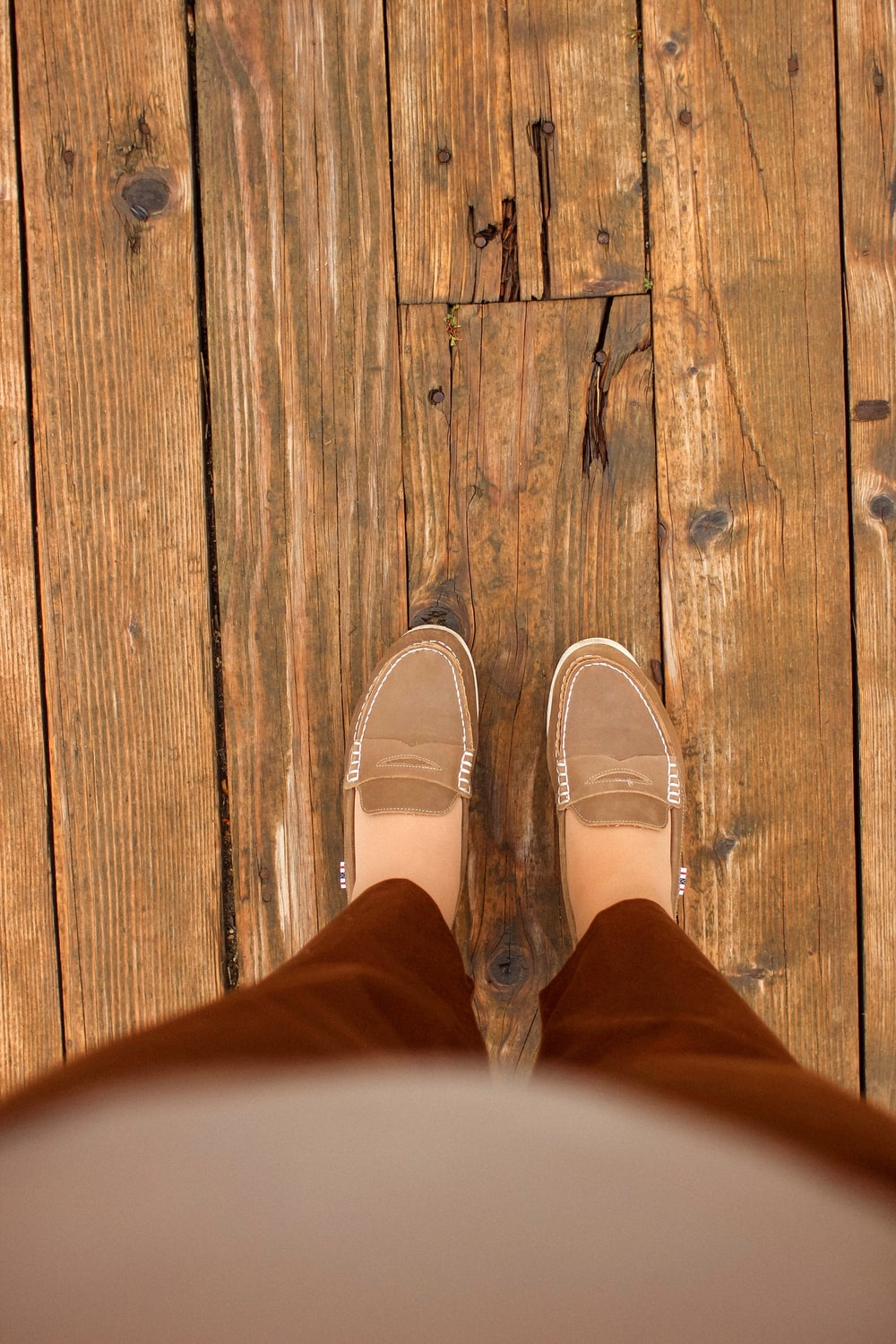 person in brown pants and white shoes