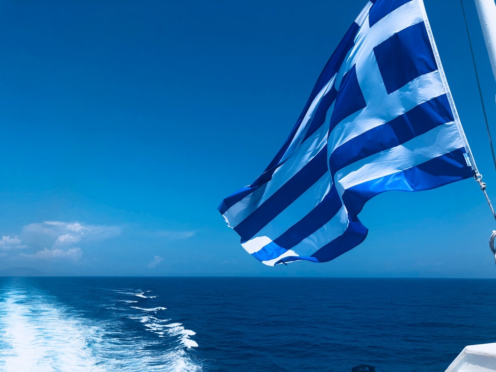 blue and white striped flag on the sea during daytime