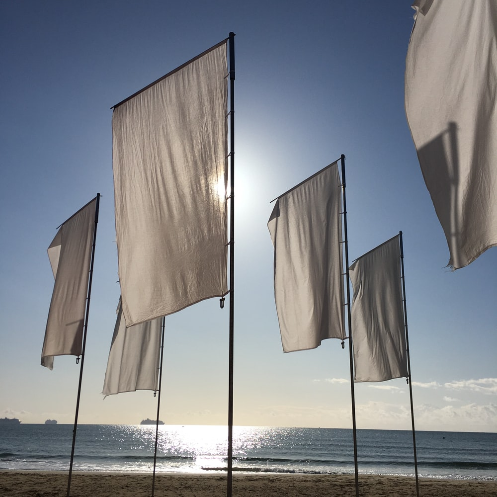 white textile hanged on wire during daytime