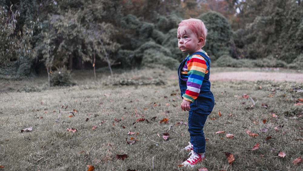 boy in red blue and green plaid dress shirt and blue denim jeans walking on grass