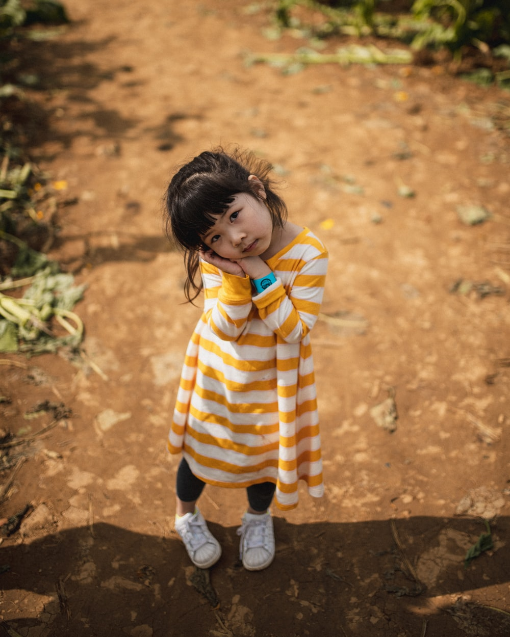 child in yellow and white striped hoodie and blue pants standing on brown soil during daytime