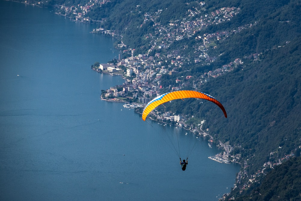 person in yellow parachute over blue sea during daytime