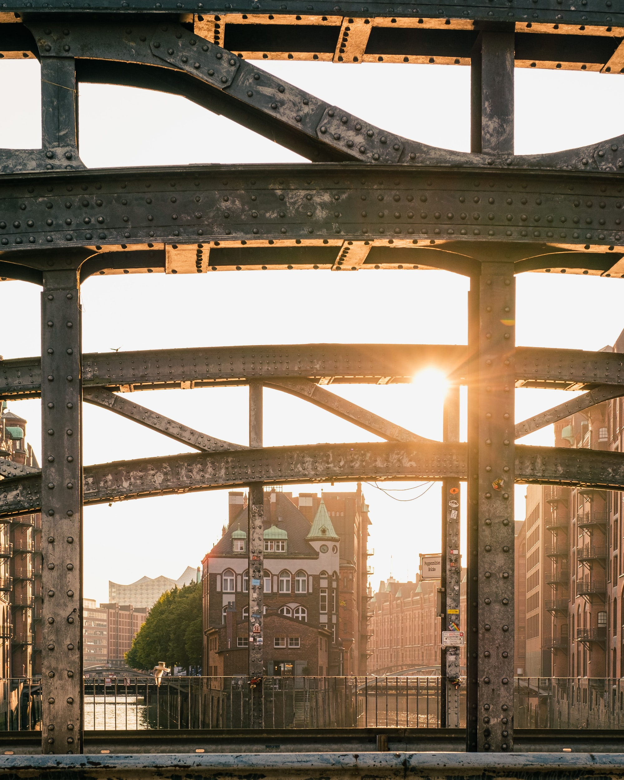 Sun shines through old bridge steel beams in Speicherstadt district of Hamburg