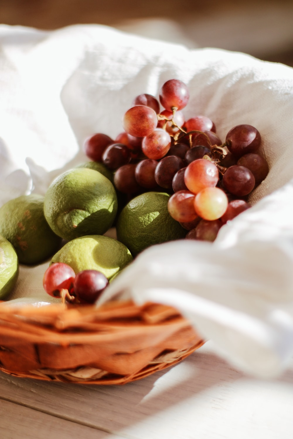 green and brown fruits on brown woven basket