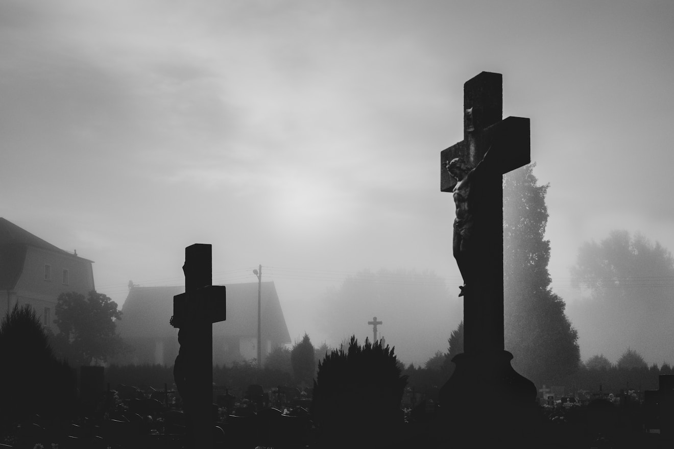 silhouette of cross under cloudy sky during daytime