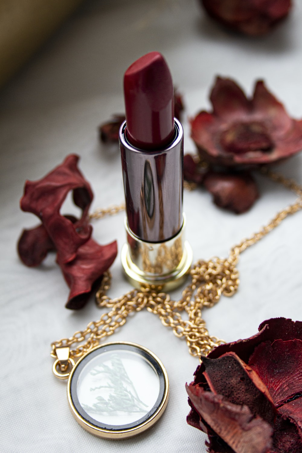 gold and red lipstick on red textile
