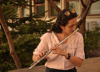 woman in white shirt playing flute