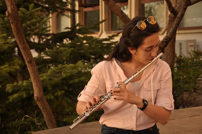 woman in white shirt playing flute flute teams background