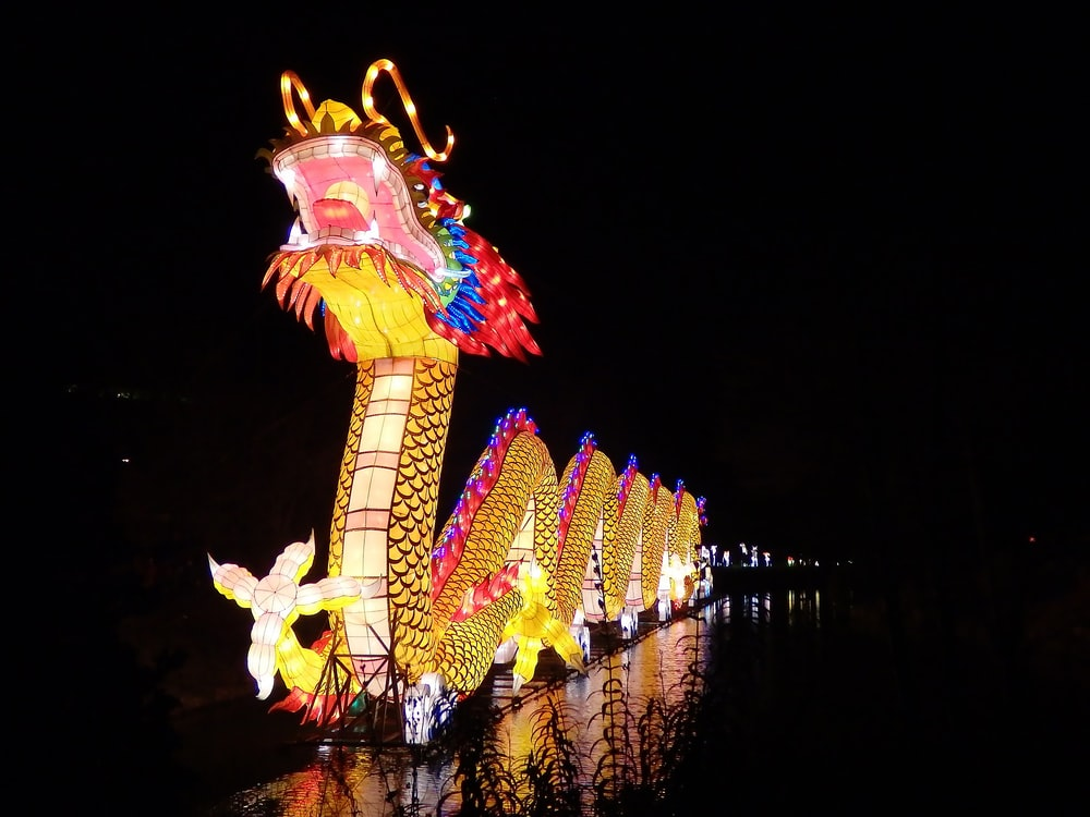 yellow and red dragon with lights on top of building
