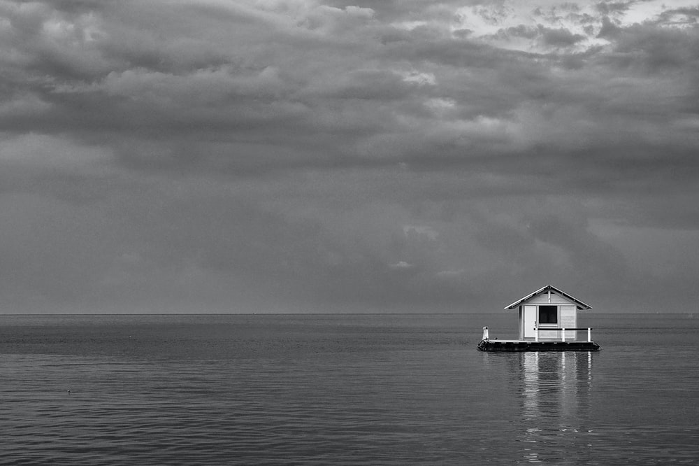 grayscale photo of house on body of water