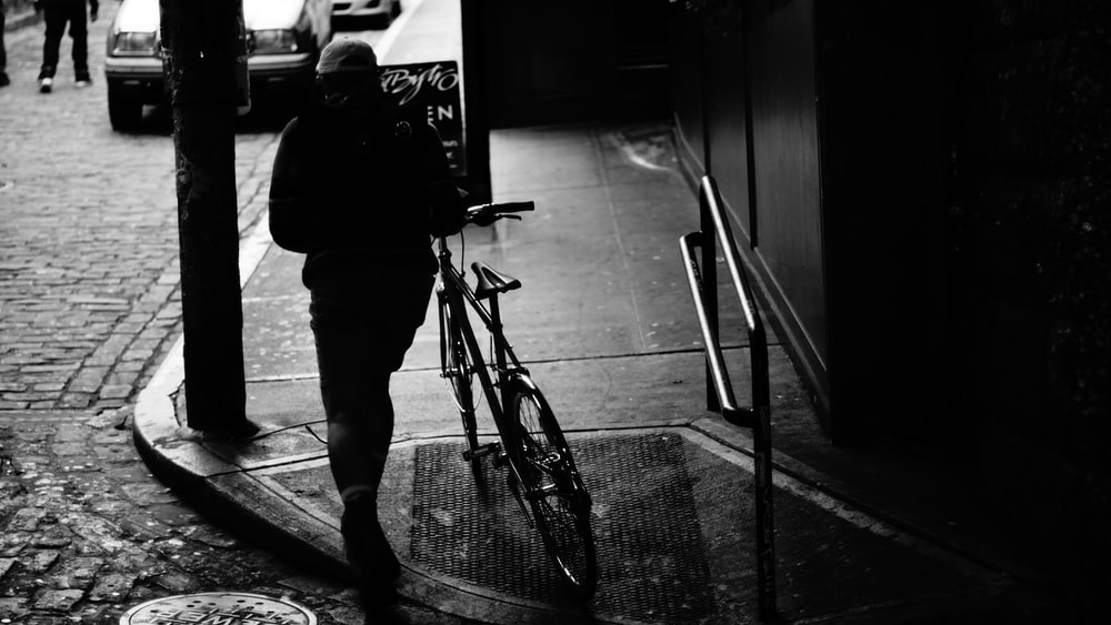 man in black jacket and pants standing beside bicycle