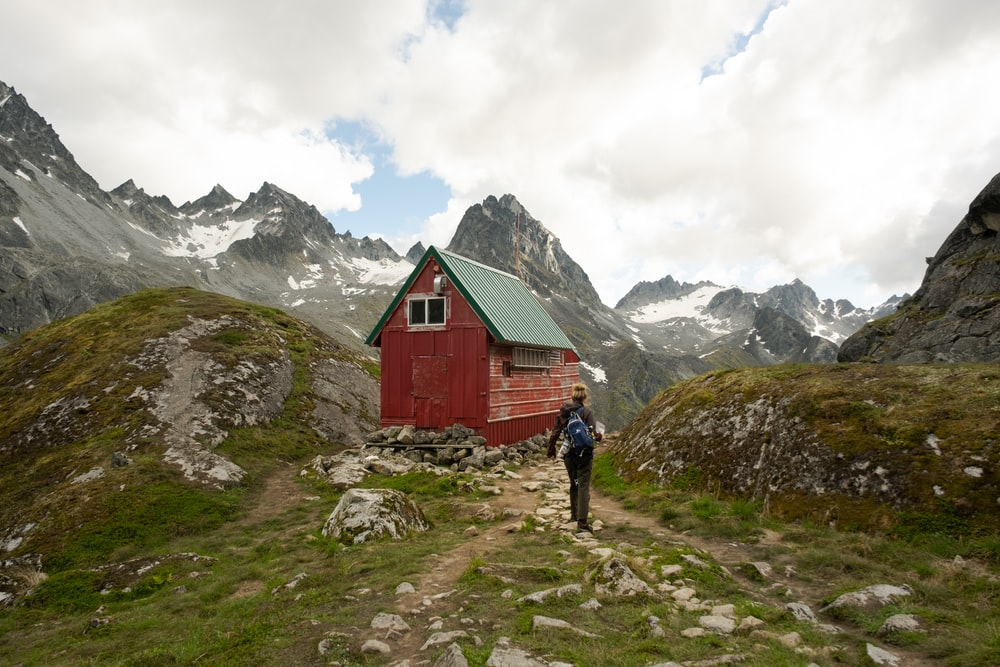 person in red jacket walking on green grass field near red wooden house during daytime
