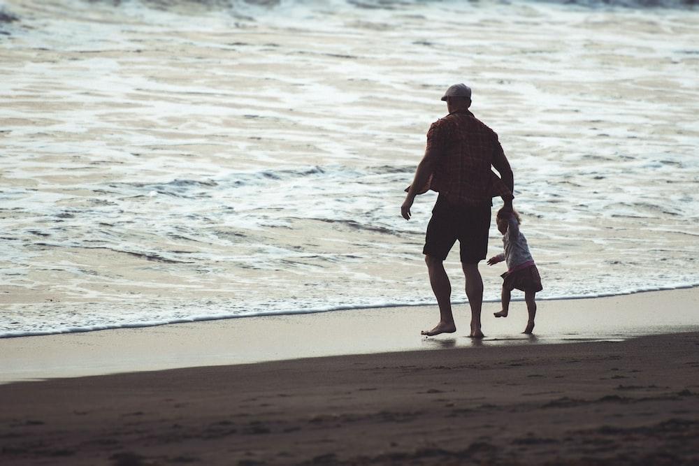 man in black shirt walking on beach during daytime