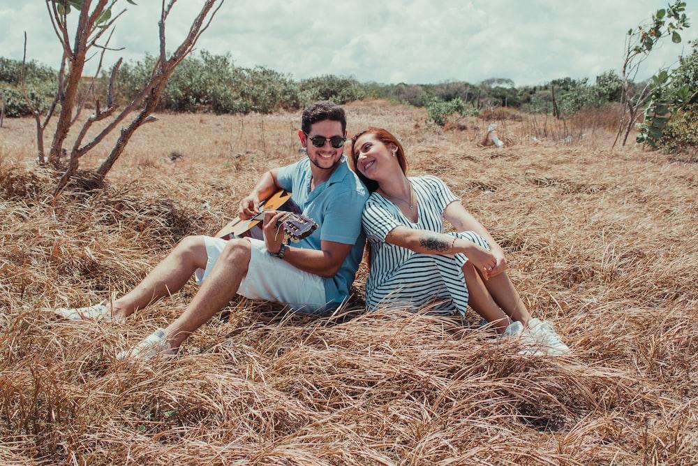 2 women sitting on brown grass field during daytime