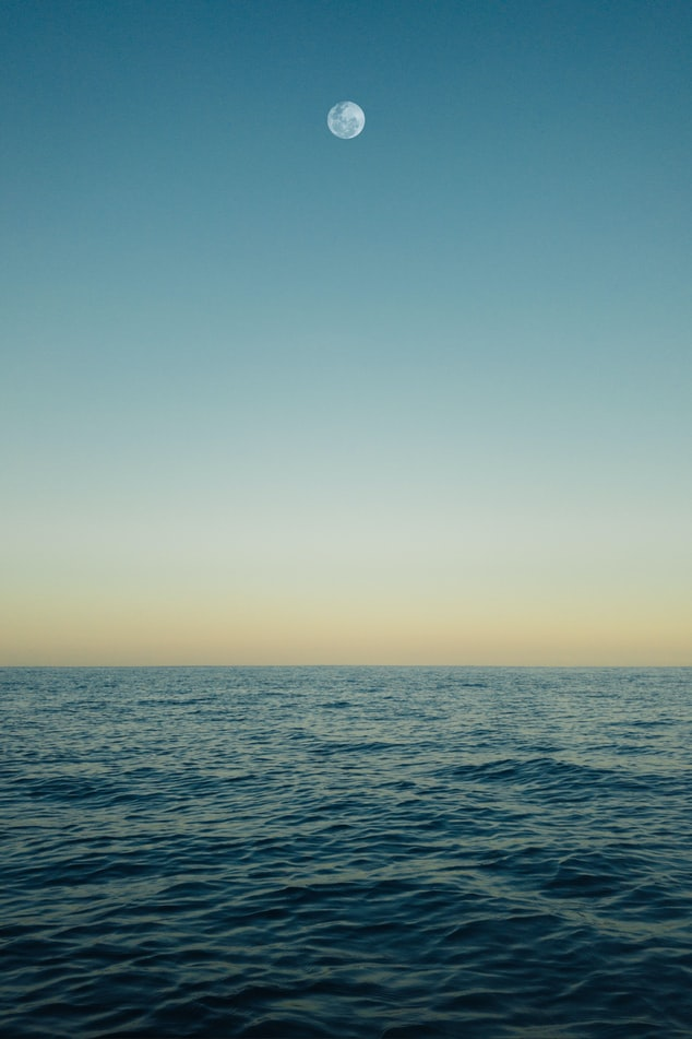A photo over the ocean, the water is choppy with a flat horizon and the full moon is visible even though it's daytime.