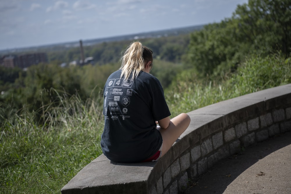 woman in black t-shirt sitting on concrete bench during daytime