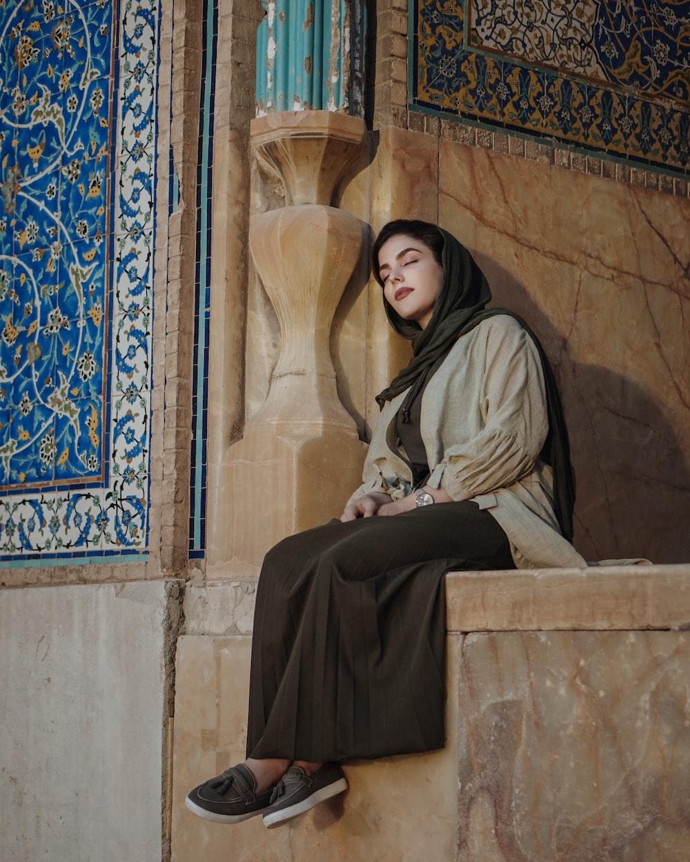 woman in black hijab sitting on brown concrete bench