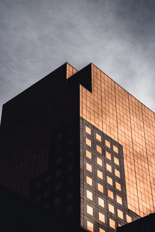 brown concrete building under gray clouds