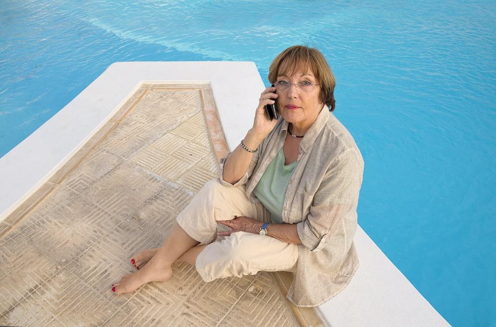 woman in brown coat sitting on brown wooden dock